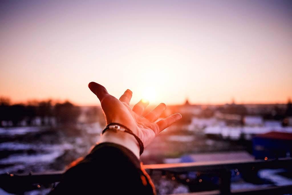 Main tendue vers le soleil et ses rayons synonymes de vitamine D