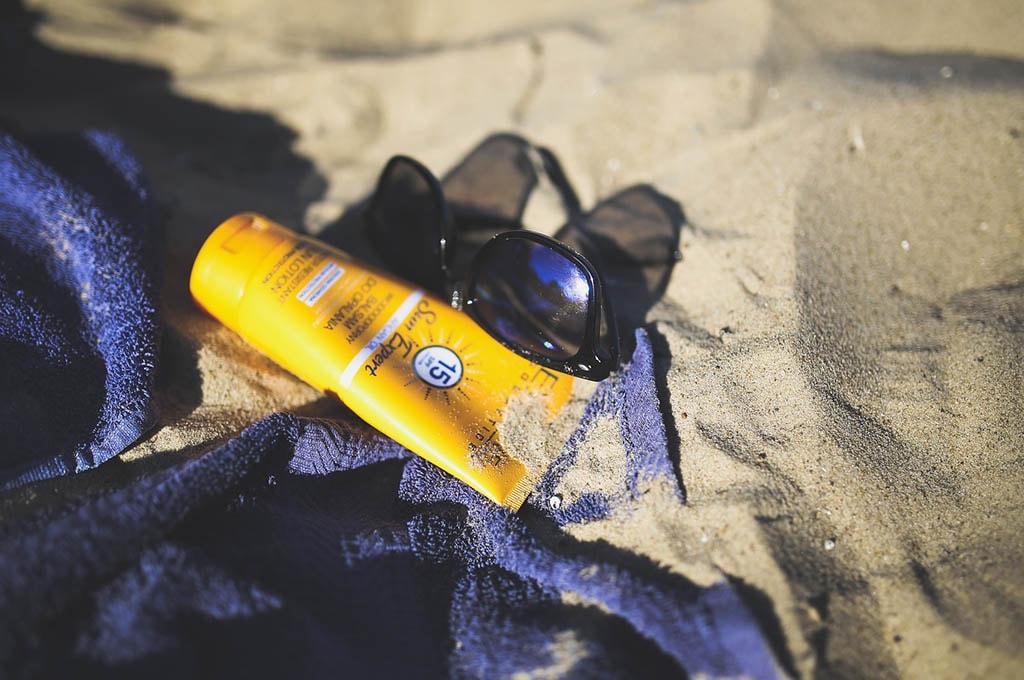 Crème et lunette de soleil sur une plage