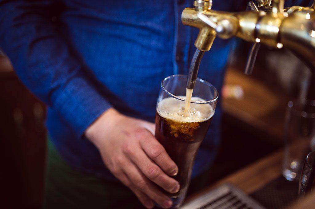 Un homme remplit une pinte de bière